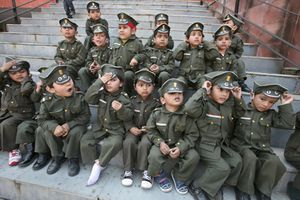 School children dressed as military soldiers sit in Chandigarh
