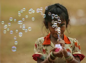 A girl selling bubble-making toys, blows bubbles to attract buyers in Mumbai.
