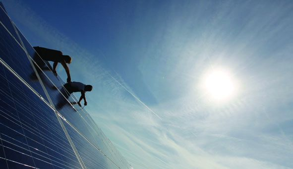 Construction workers fix solar panels for solar power plant near Olching.