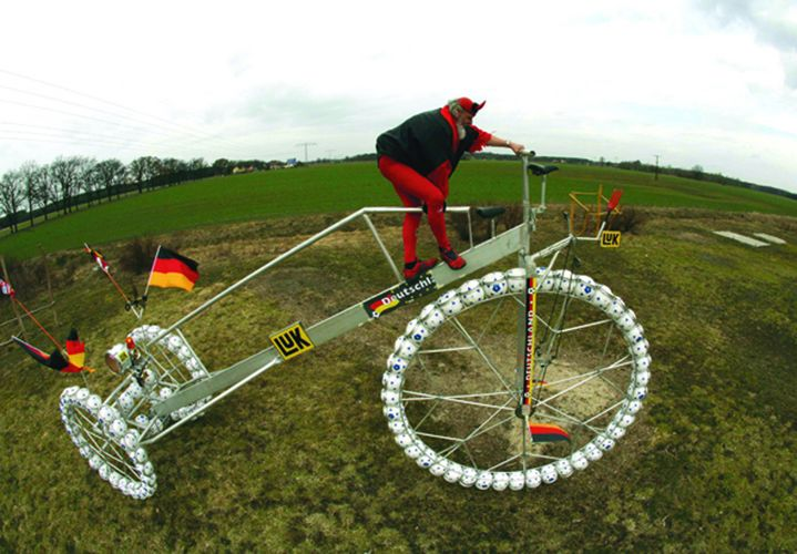 "Cycling fan El Diablo climbs on his giant ""soccer bicycle"" in Storkow. REUTERS/Pawel Kopczynski"