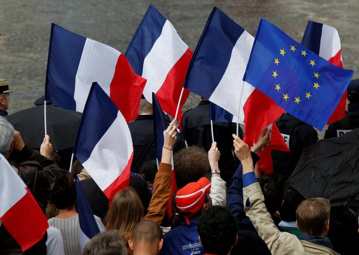 People holds French and European flags