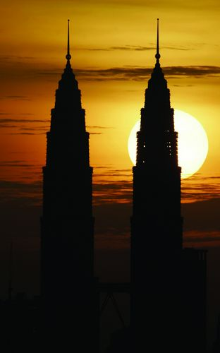 The sun sets behind the Petronas Twin Towers in Kuala Lumpur