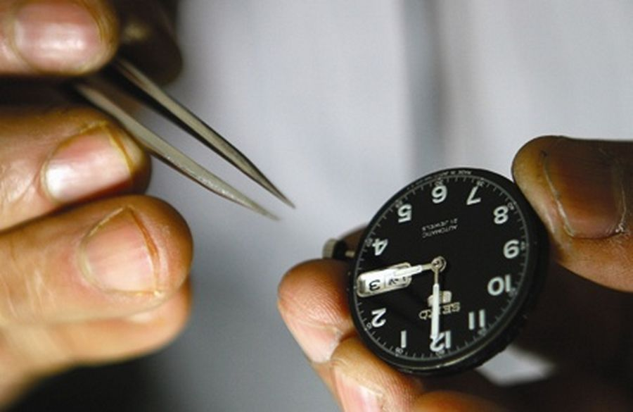 A man holds tweezers while repairing a watch at his workshop in Srinagar.