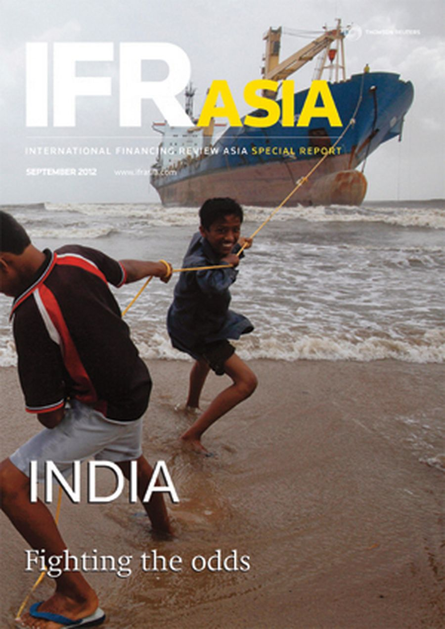 Youths tug at a rope line used to fasten a cargo ship, which ran aground, to the shore in Mumbai