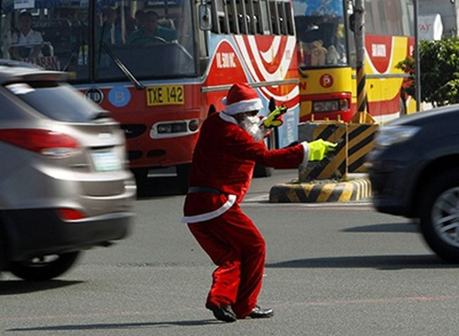 Ramiro Hinojas, 47, a traffic enforcer, wears a Santa Claus costume as he directs traffic along a main street in Pasay city, metro Manila.