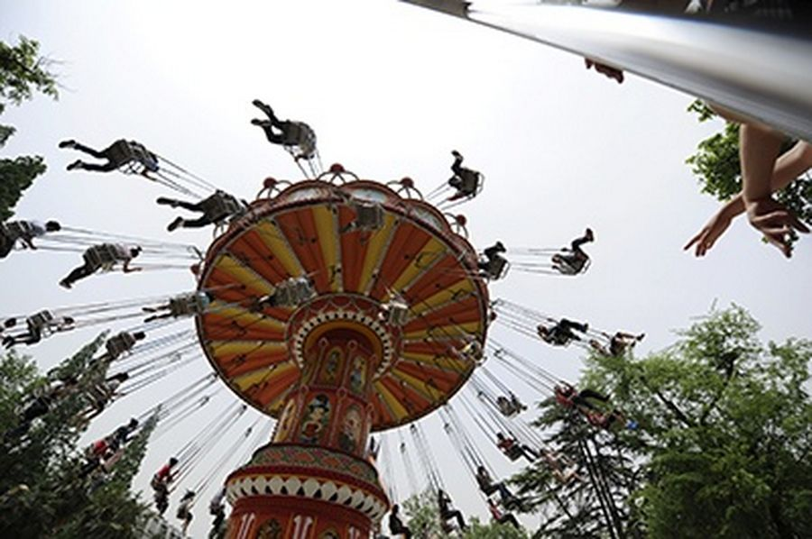 People ride on a chair-o-plane at a park on May Day holiday in Hefei, Anhui province.