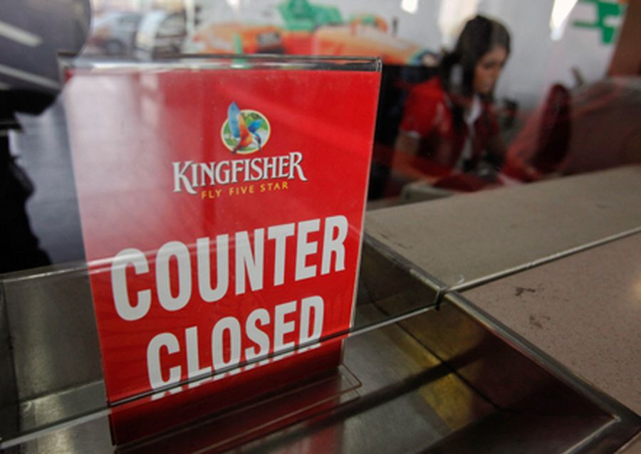 An employee of Kingfisher Airlines works next to a counter closed sign at the carrier's booking of
