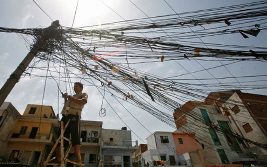A man stands on a stepladder to fix tangled overhead electric power cables at a residential area in