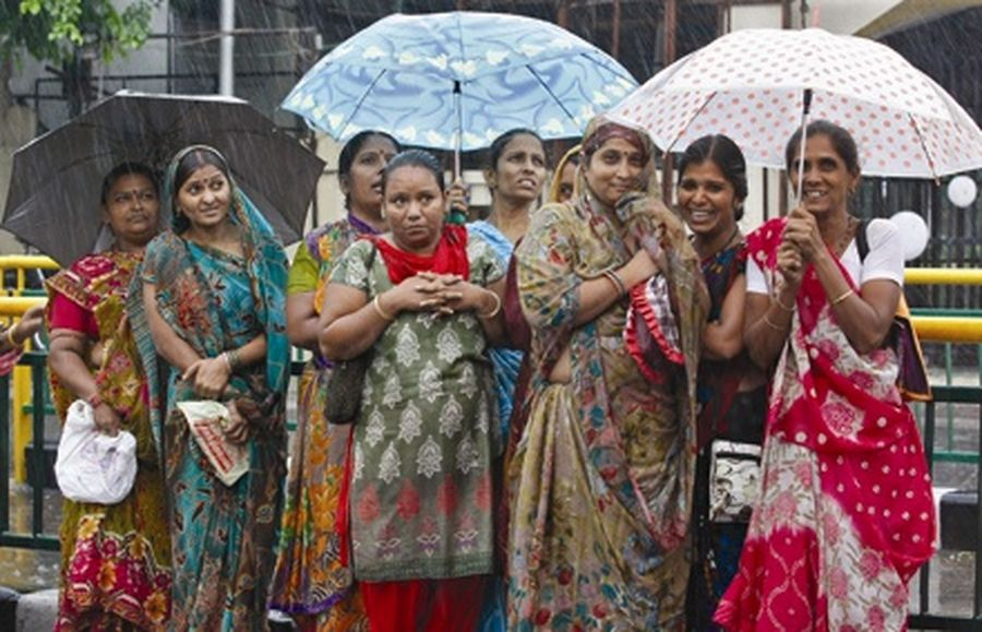 Women hold umbrellas to protect themselves from a heavy rain shower as they stand at a bus stop in the western Indian city of Ahmedabad.